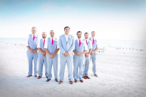 Groomsmen wearing fuchsia ties during a beach wedding in Sarasota Florida.