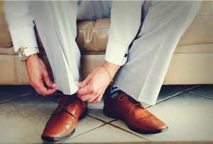 A light colored suit with tan dress shoes are a good traditional-style choice for a Florida beach wedding.