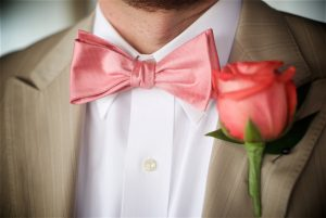 Groom wears a colored bow tie and boutonniere for his Florida beach wedding.