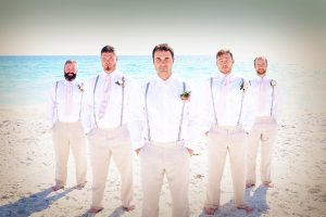 Groomsmen wearing casual khahki pants, white shirts and suspenders during a Florida beach wedding in Sarasota.