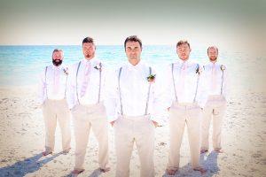 Groomsmen wearing casual khahki pants, white shirts and suspenders during a Florida beach wedding in Sarasota.