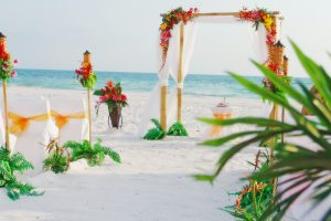A tropical Hawaiian themed beach wedding ceremony on Siesta Key Beach in Sarasota Florida