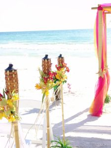 Three tropical Hawaiian style tiki torches line the isle of a gulf beach wedding in Sarasota Florida