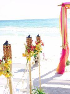 Three tropical Hawaiian style tiki torches line the isle of a gulf beach wedding in Sarasota Florida