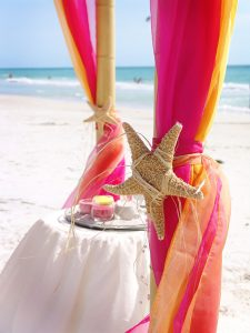 Tropical Hawaiian themed starfish tie back and sand ceremony table during a destination beach wedding on Siesta Key Beach
