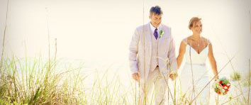 bridal couple holds hands thru the sea oats at their anna maria island beach wedding