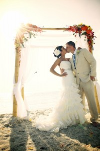 A groom in a light colored suit and tie kissing his bride during a beach wedding in Sarasota Florida